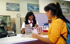 African American female US Postal Service employee selling stamps to teen girl in post office, Oakland, California